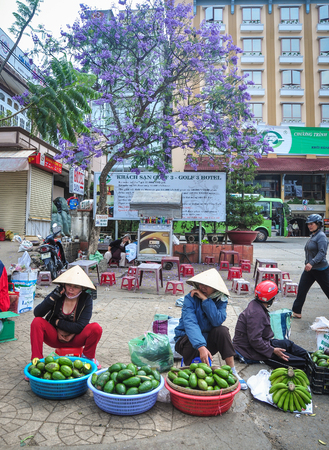 Dalat, Vietnam - Apr 5, 2013. People selling fruits on street in Dalat, Vietnam. Da Lat is located 1500 m above sea level on the Langbian Plateau. Editorial
