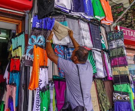 Port Louis, Mauritius - Jan 13, 2017. A man selling clothes in Port Louis, Mauritius. Port Louis is the country economic, cultural and political centre. Editorial