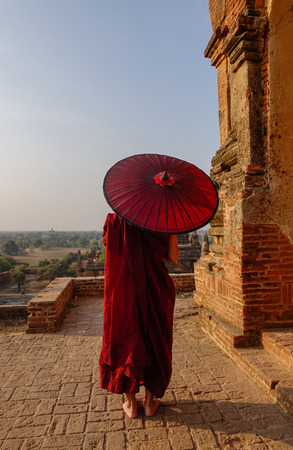 A young monk standing at Buddhist pagoda in Bagan, Myanmar. Фото со стока