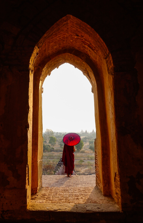 A young monk standing at ancient Buddhist temple in Bagan, Myanmar.