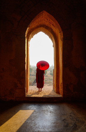 A young monk coming to ancient Buddhist temple in Bagan, Myanmar.