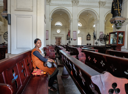 Galle, Sri Lanka - Sep 9, 2015. A young woman praying at the church in Galle, Sri Lanka. Galle was the main port on the island in the 16th century. Editorial