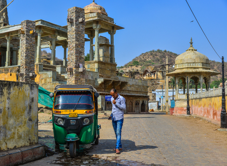 Jaipur, India - Nov 3, 2017. A tuk tuk taxi with driver waiting for passengers on street near Amber Fort in Jaipur, India. Editorial