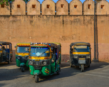 Jaipur, India - Nov 3, 2017. Tuk tuk taxis waiting for passengers on street near Amber Fort in Jaipur, India.