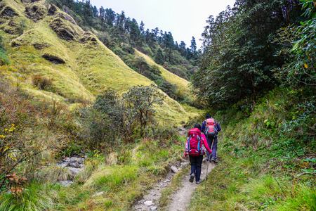 Young travelers with backpack walking on trail of Annapurna Circuit Trekking at autumn in Khopra, Nepal. Stock Photo