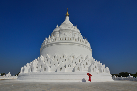 A Buddhist novice monk walking around the big stupa of white temple in sunny day.