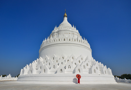 A Buddhist novice monk walking around the white stupa in sunny day. Stock Photo
