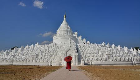 A Buddhist novice monk with a red umbrella coming to white stupa in sunny day.