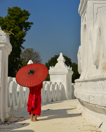 A Buddhist novice monk with a red umbrella walking at the white temple in sunny day.