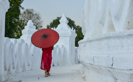 A Buddhist novice monk with a red umbrella walking at the white temple. Stock Photo