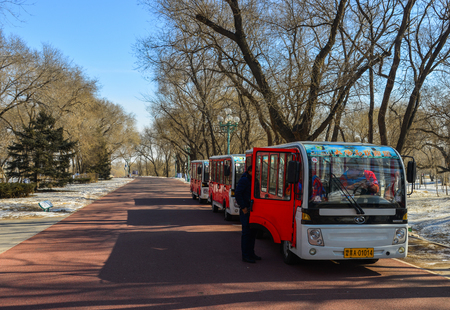 Harbin, China - Feb 22, 2018. Tourist bus waiting at tree park in Harbin, China. Harbin is largest city in the northeastern region of China.
