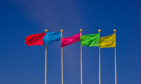 Colorful multicolored flags against the blue sky in sunny day. Фото со стока
