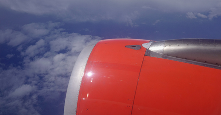Flying with an airplane, view of the wings, engine, sky and the clouds through the aircraft window.