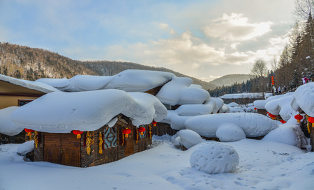 Wooden houses covered by snow at mountain village in Harbin, China. Stock Photo