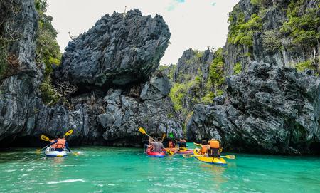 Palawan, Philippines - Apr 5, 2017. Tourists paddling kayak on blue sea in Palawan, Philippines. Palawan is the island of idyllic tropical beauty.
