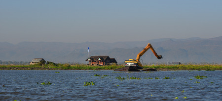 Inle Lake, Myanmar - Feb 7, 2018. Excavator dredges and cleans up the Inle Lake, Myanmar. Inle Lake a freshwater lake located in Shan State. Editorial