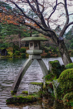 Famous Kotoji two-legged stone lantern beside pond at Kenroku-en garden in Kanazawa, Japan. Stock Photo