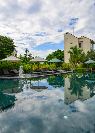 Hoi An, Vietnam - Jul 20, 2018. Swimming pool of luxury resort in Hoi An, Vietnam. Hoi An is a city on central coast known for its well-preserved Ancient Town.