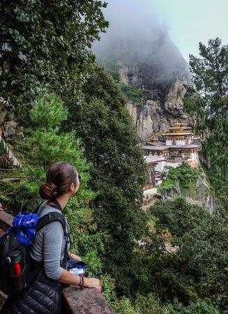 A woman looking at the Taktsang Palphug Monastery (Tiger Nest) on misty mountain in Paro, Bhutan.
