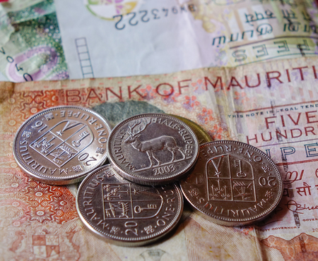 Mauritius Rupee (MUR) notes and coins with red background - close up.