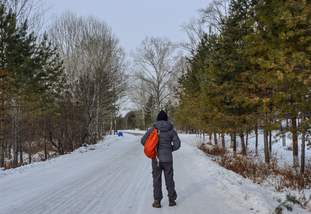A man walking on snow road at deep forest in winter.