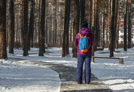 A woman walking on snow road at deep forest in winter.