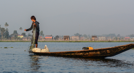 Inle, Myanmar - Feb 14, 2016. Burmese man using the unique methods of rowing and catching fish on Inle Lake. Inle is one of the highest lake at an elevation of 880m. Redakční