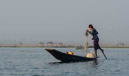 Inle, Myanmar - Feb 14, 2016. Burmese man using the unique methods of rowing and catching fish on Inle Lake. Inle is one of the highest lake at an elevation of 880m. Editorial