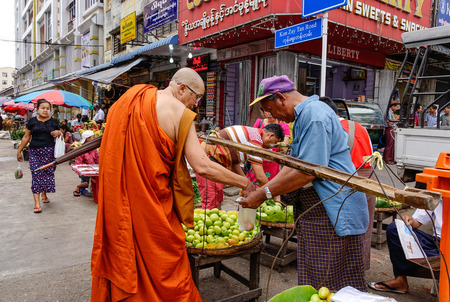 Yangon, Myanmar - Feb 26, 2016. A monk at street market in Yangon, Myanmar. Yangon is Myanmar largest city and its most important commercial centre.