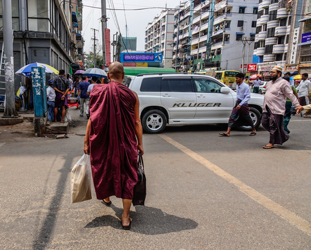 Yangon, Myanmar - Feb 26, 2016. A monk walking on street of Yangon, Myanmar. For many years, motorbikes have been banned in Yangon. Redakční