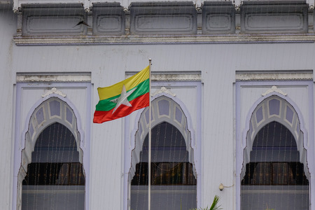 Myanmar national flag with old building (Yangon City Hall) background.