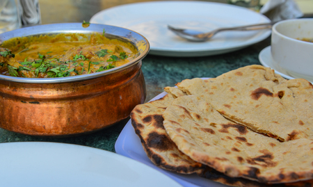 Butter chicken curry with Indian bread (roti) on table at local restaurant.