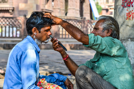 Jodhpur, India - Nov 6, 2017. A man gets a shave at a street barber shop in Jodhpur, India. Jodhpur is the second largest city in state of Rajasthan.