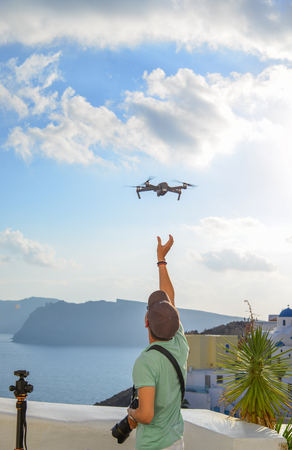 A traveler using drone at Oia Town in Santorini, Greece.
