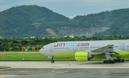 Da Nang, Vietnam - Jul 23, 2018. A Boeing 777-200ER airplane of JinAir taxiing on runway of Da Nang International Airport (DAD). 新聞圖片