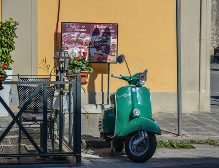 Pisa, Italy - Oct 18, 2018. A green Vespa at old town of Pisa, Italy. Pisa contains more than 20 other historic churches, and various bridges across the Arno. Sajtókép