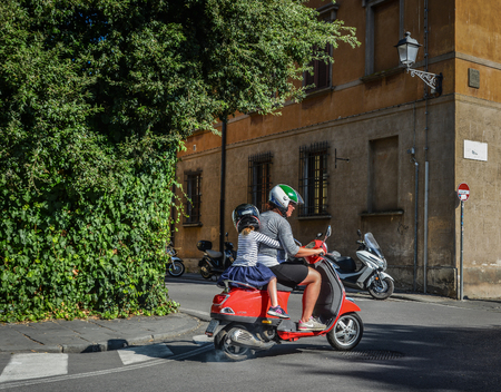 Pisa, Italy - Oct 18, 2018. People riding Vespa on street in Pisa, Italy. The Vespa has evolved from a single model motor scooter manufactured in 1946.