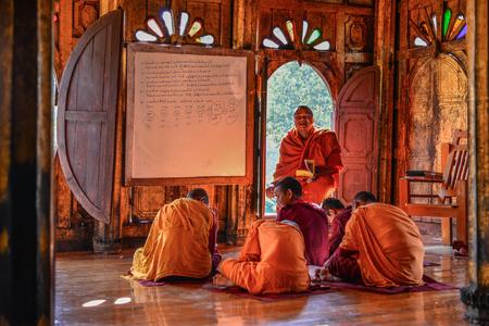 Nyaungshwe, Myanmar - Feb 8, 2017. Young Samaneras (novice monks) sitting and studying in prayer hall of Shwe Yan Pyay Monastery. Editöryel