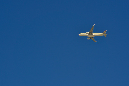 Passenger airplane flying in the blue sky. Aviation background with copy space.