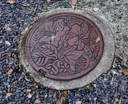 Takayama, Japan - Dec 30, 2015. Manhole drain cover on the street in Takayama, Japan. Takayama is a city in Japan mountainous Gifu Prefecture.