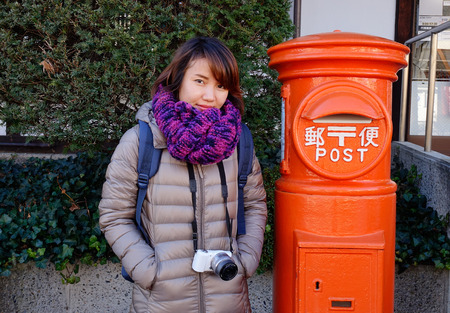 Nagano, Japan - Dec 30, 2015. Young traveller woman portrait with red post box in Nagano, Japan.