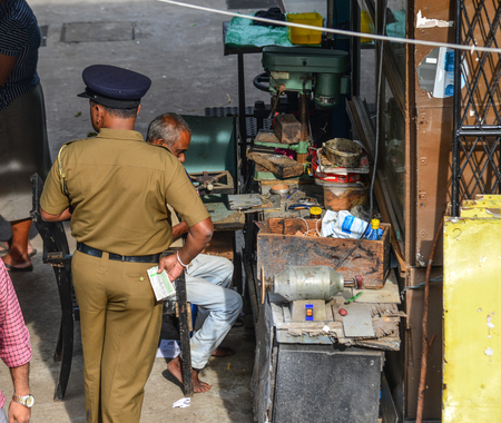 Colombo, Sri Lanka - Dec 12, 2018. A police man standing at the old shop in Colombo, Sri Lanka. Editorial