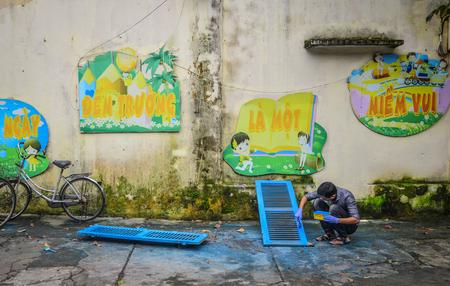 Hoi An, Vietnam - Jan 20, 2019. A man painting wooden doors on street in Hoi An, Vietnam.