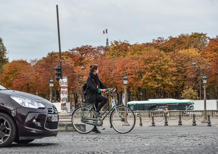 Paris, France - Oct 3, 2018. Woman biking on street of Paris, France. Paris is a global center for art, fashion, gastronomy and culture. Редакционное