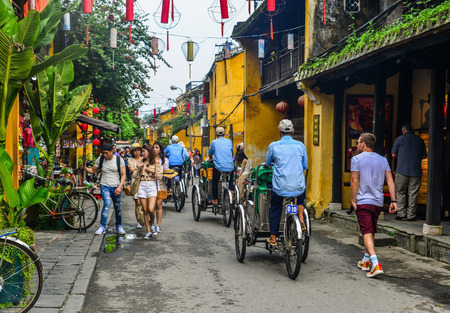 Hoi An, Vietnam - Jan 20, 2019. Cyclo (traditional rickshaw) carrying tourists on main street of old town in Hoi An, Vietnam.