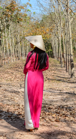 An Asian in traditional dress (Ao Dai) with a conical hat, walking on rural road in Southern Vietnam.