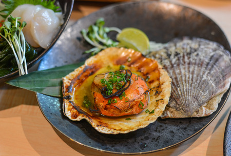 Grilled fresh scallop with soil sauce in hard shell.