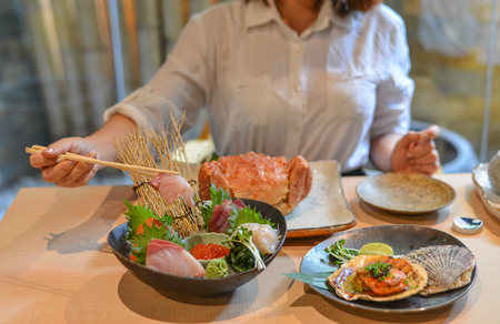 Woman eating and enjoying Japanese meal in luxury restaurant.