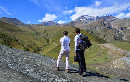 Kazbegi, Georgia - Sep 24, 2018. Happy couple hiking in mountains of Kazbegi, Georgia. Mount Kazbegi is located on the northern slopes of the Caucasus range.