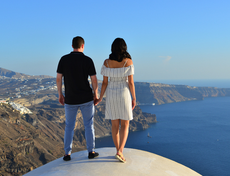 A young couple standing and looking at the sea in Santorini Island, Greece. Banco de Imagens - 119987957